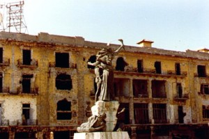 Photo of a burned out building behind the central sculpture in Martyr's Square, Beirut, 1982