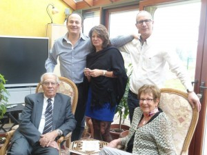 The family faces the camera, Albert and Janine seated, with their trhree grown children standing behind them.