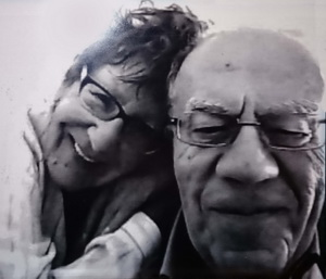 Black-and-white close-up photo of Albert and Jeanine Samaha. They are both older people and each wear spectacles. Jeanine leans on Albert's shoulder. They are both smiling. She is looking directly at the camera, while Albert is looking down as he focuses on something in front of him.