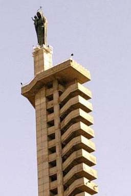 View from the ground of a grey statue of the Virgin atop a tall sandstone-coloured building