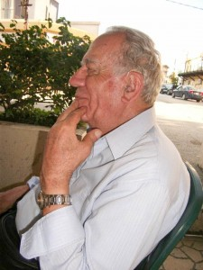 Photo of left side profile of Albert Samaha sitting on a ground-floor terrace with his back to the road. A divider hedge is visible on th other side of him. His left had is raised to his chin in Thinker pose as he smiles gently, as though enjoying a conversation or a thought.