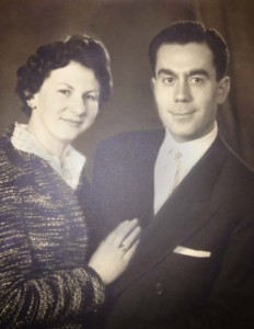 Black-and-white photo of a handsome couple, smiling. Jeanine is turned slightly towards Albert, with her right hand on his chest.