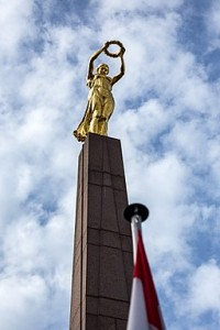 Gold statue of a woman in a flowing dress holding a golden wreath aloft as she looks down from her stone pedestal